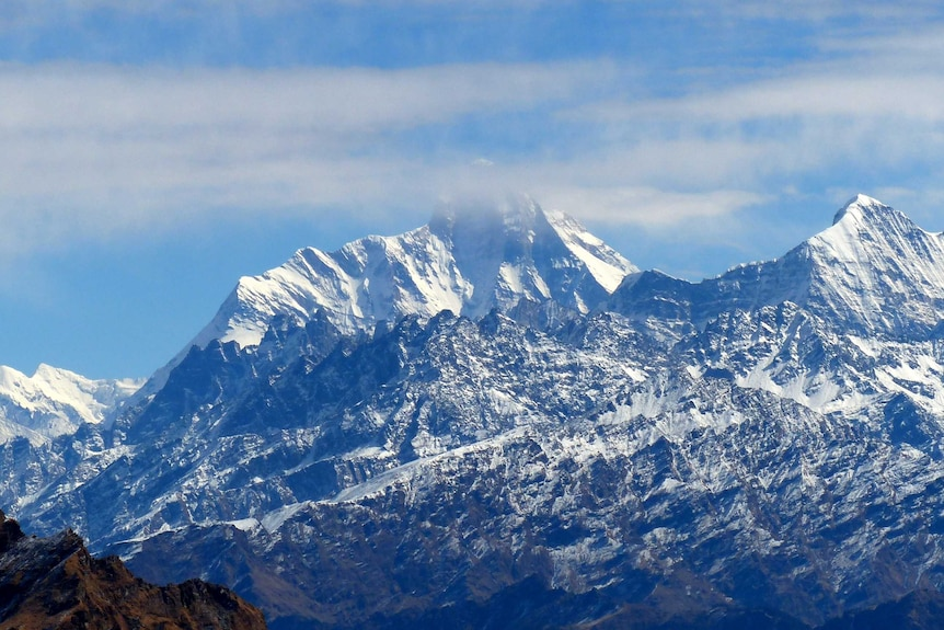 Clouds obscure the top of a large snow-capped mountain.