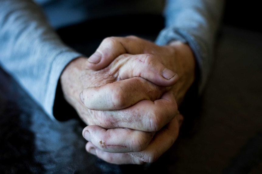 Generic older woman's worn hands clasped