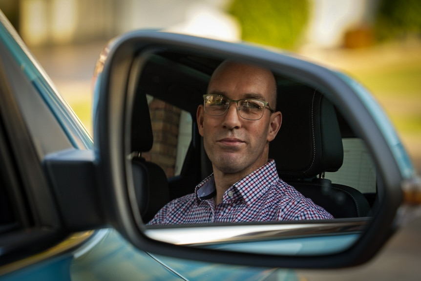 The side mirror reflection of a man with glasses sitting in a blue car