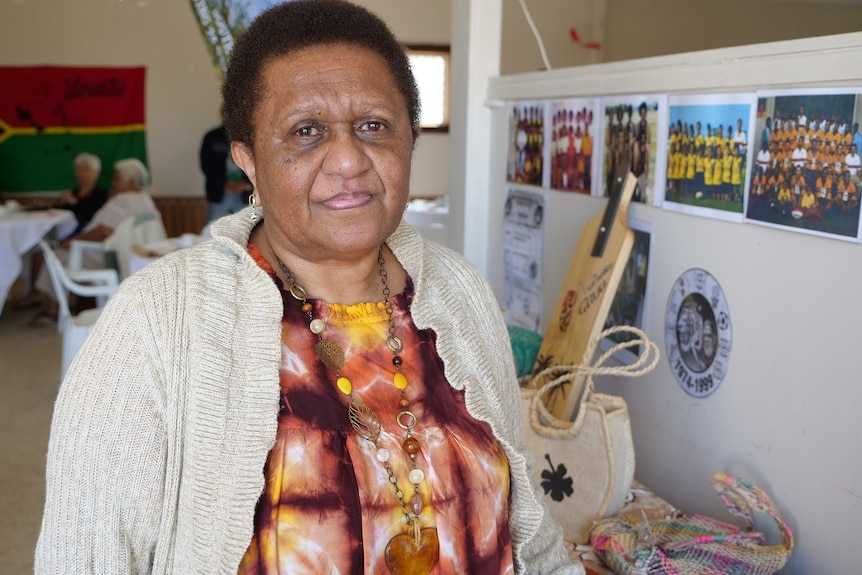 Aunty Roz Wallace stands in a room with Vanuatu themed props beside her.