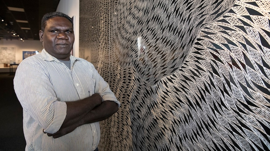 The Indigenous artist stands with his artwork, etched into an aluminium board