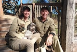 Warrawong Sanctuary owners Narelle MacPherson and David Cobbold sit on steps with a dog.