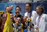 A grinning Australian beach volleyballer holds her phone to take a picture of her, her partner and the other Olympic medallists.