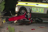 A crashed motorcycle lays on the road next to a police car