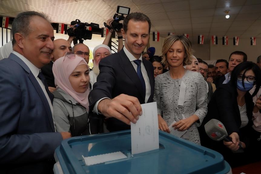 Bashar al-Assad puts a ballot in a box.