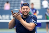 Australian wheelchair tennis star Dylan Alcott wears a beaming smile as he holds the US Open trophy in his hands.