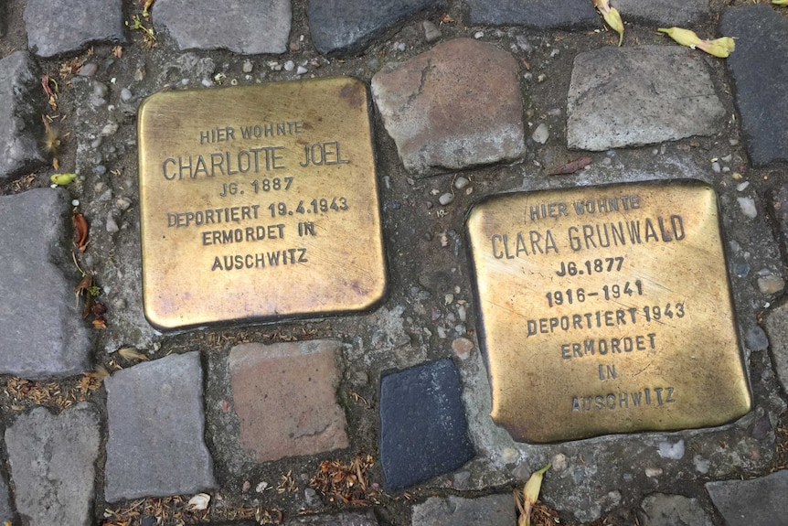 """Two brass plates set in the cobblestones of a Berlin footpath. They state """"Here lived"""" and then give the name of a person."""