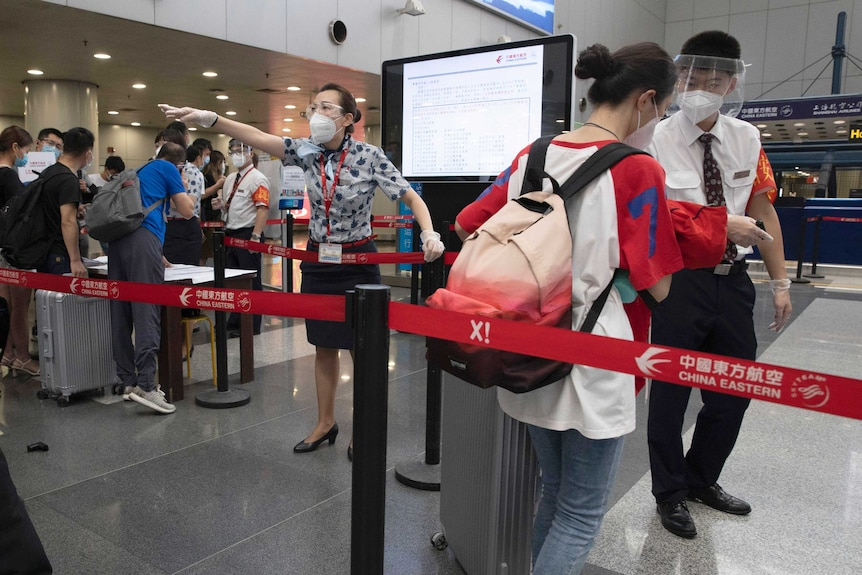 Airport staff redirect a traveller at a checkpoint for people from high risk areas to present test results before checking in