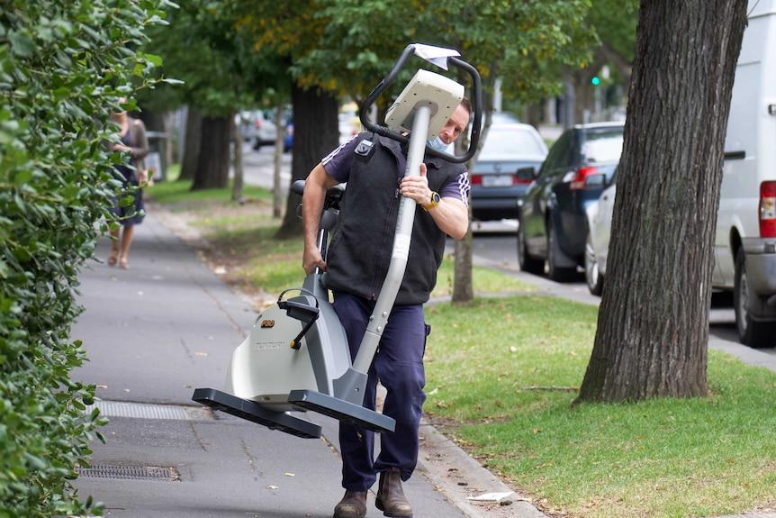 A man carries an exercise bike along a footpath.