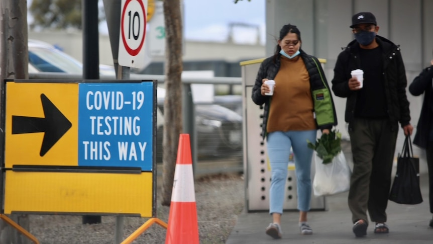 Two people walk near a sign saying 'COVID-19 testing this way'.