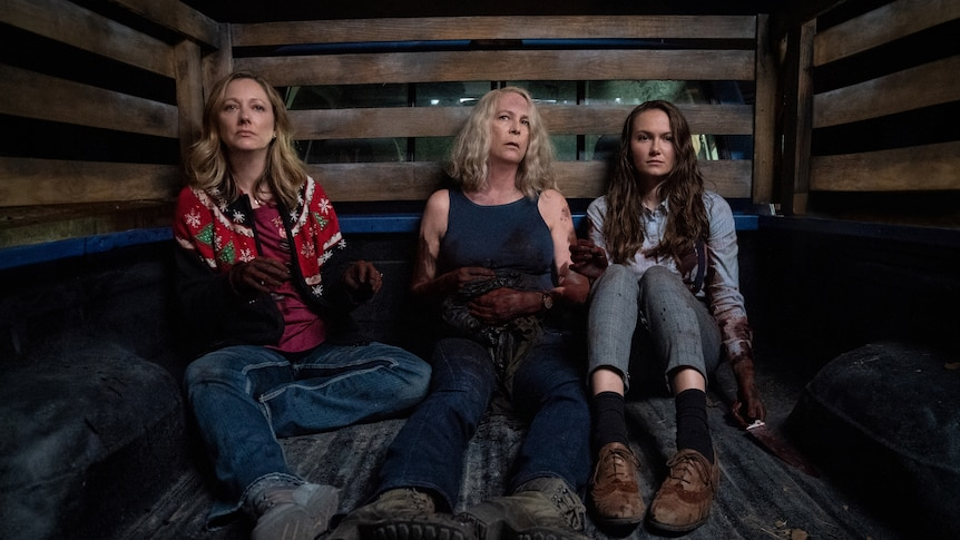 Three women - one in her mid 40s, the middle in her 60s and the third in her 20s - sit in a truck covered in blood