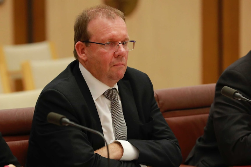 Grant Hehir sits with his arms crossed at a table looking at politicians out of the picture