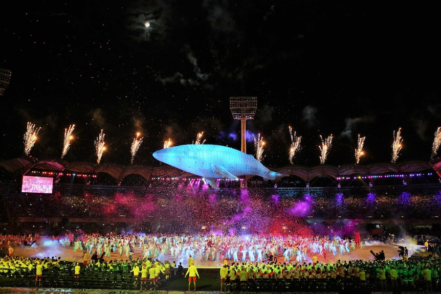 A large whale figure floats above the stadium while confetti and fireworks shoot out