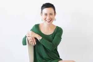 Woman with short, dark hair wearing green dress sits sideways on a chair
