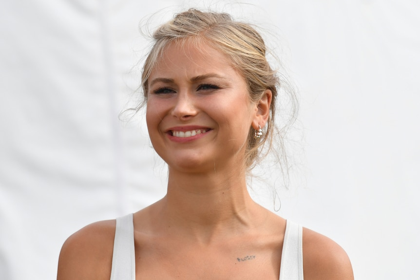 Australian of the Year Grace Tame smiling in front of a white background while wearing a white dress.