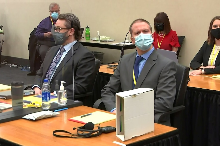 A middle-aged man in grey suit and face mask sits beside another man in dark suit in courtroom.