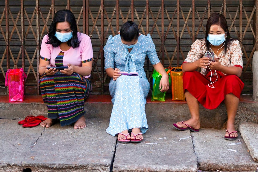 Three women in face masks sitting on a road side looking at their phones