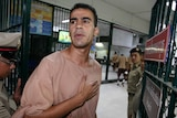 Hakeem Al Araibi gestures to his supporters outside of court in Bangkok.