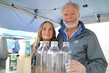 two farmers stand behind a row of glass bottles inside a tent