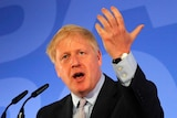 Boris Johnson at a pulpit with open mouth and raised hands.