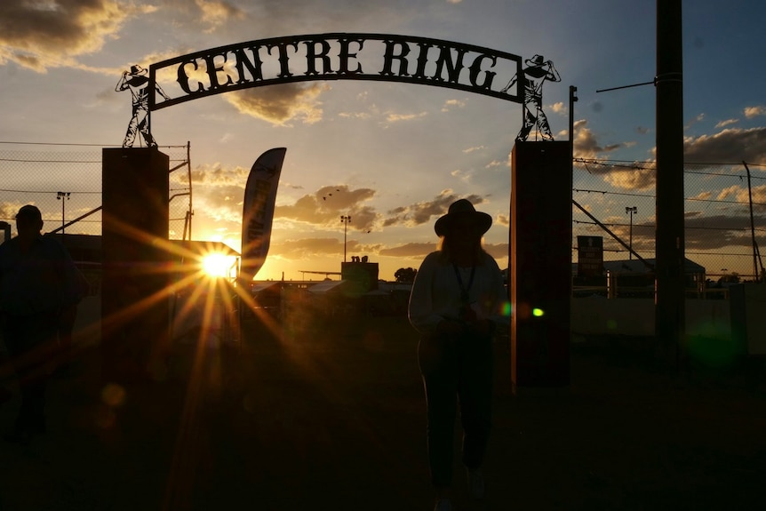 Sunset through centre ring at Beef Australia 2021, silhouette of a woman wearing a hat.