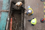 Three workers wearing high vis and hard hats looks over a trench.