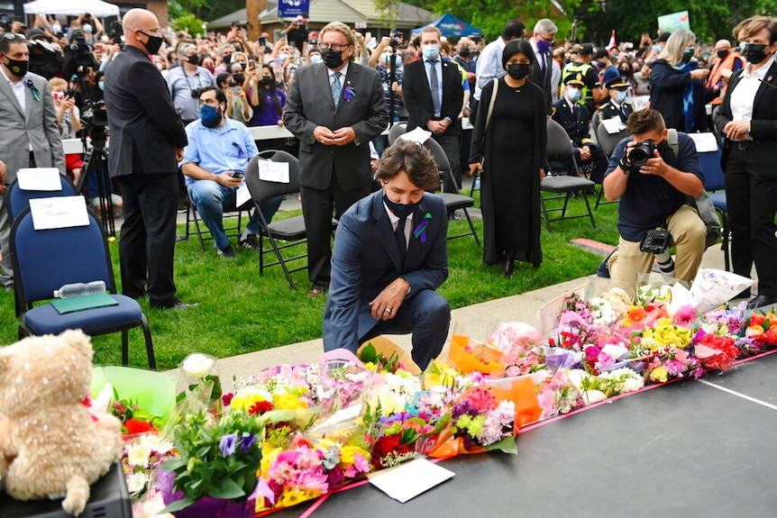 Canadian Prime Minister is pictured kneeling as he lays down flowers outside at a vigil outside of the London Muslim Mosque.