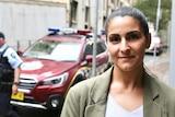 AFP Digital Forensic team member Jennifer Garcia stands in front of police cars and two AFP officers