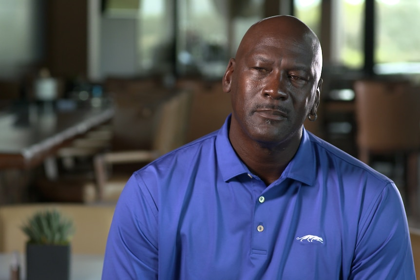 Michael Jordan wears a blue polo shirt seated in interview chair