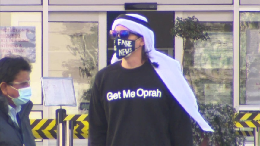 A man wearing a face mask which says 'fake news' and a t-shirt which says 'Get Me Oprah'.