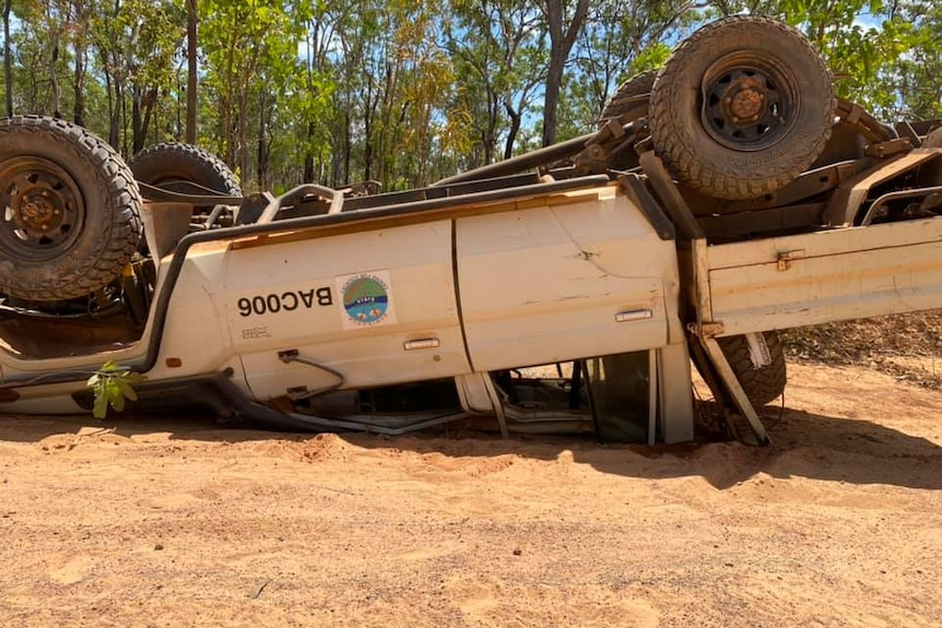 A white Toyota Landcruiser 4WD is seen overturned in sand.