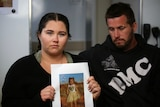 A woman holding a picture of a small girl, next to a man.
