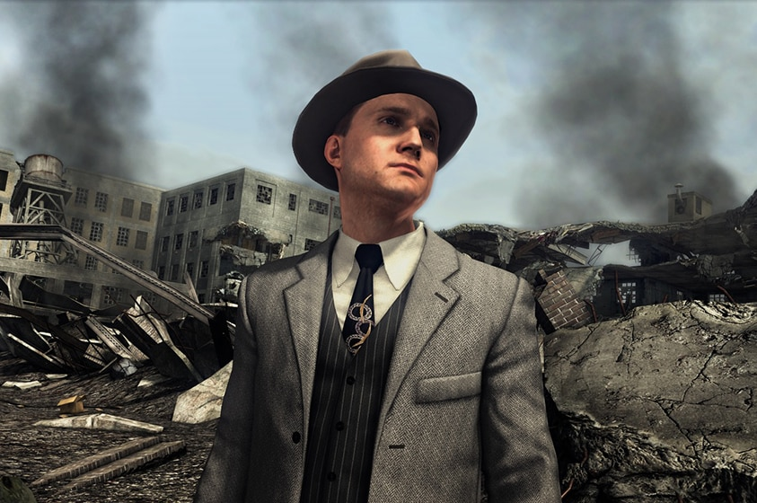 In a scene from a video game a man in American 1940s hat and suit stands among building ruins as black smoke rises to the sky.