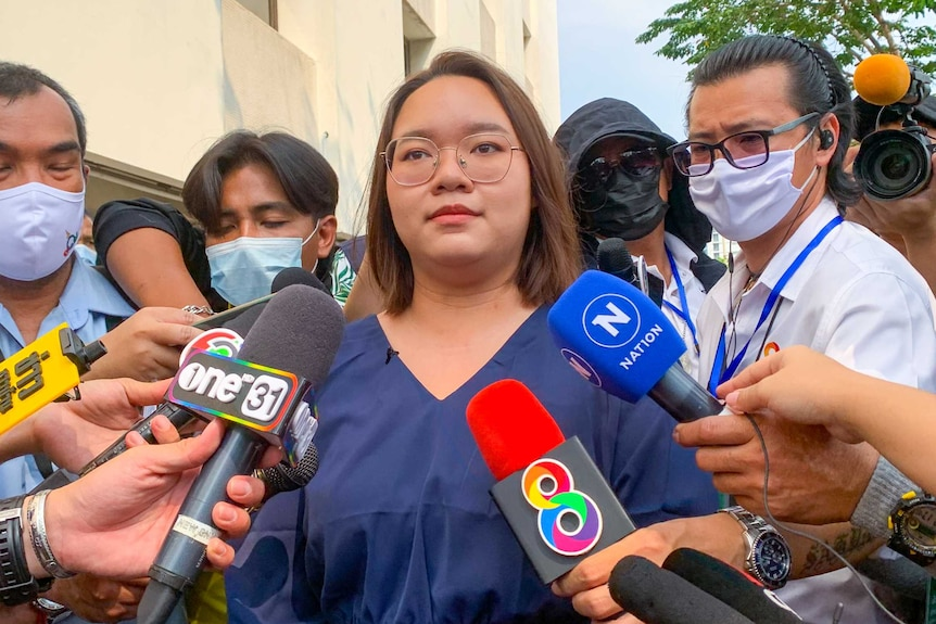 A young woman stands surrounded by journalists holding microphones under her face