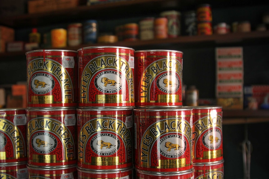 Tins of treacle stacked on top of one another.
