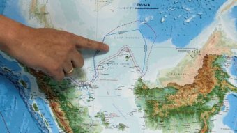 A person points to a map of the South China Sea above Indonesia.