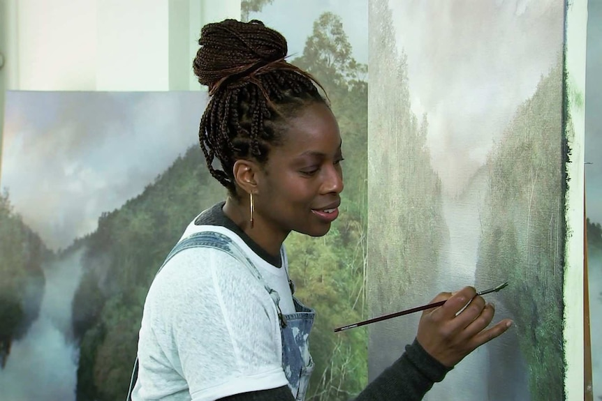 Melanie McCollin-Walker holds a small paintbrush in front of a large painting of a landscape.