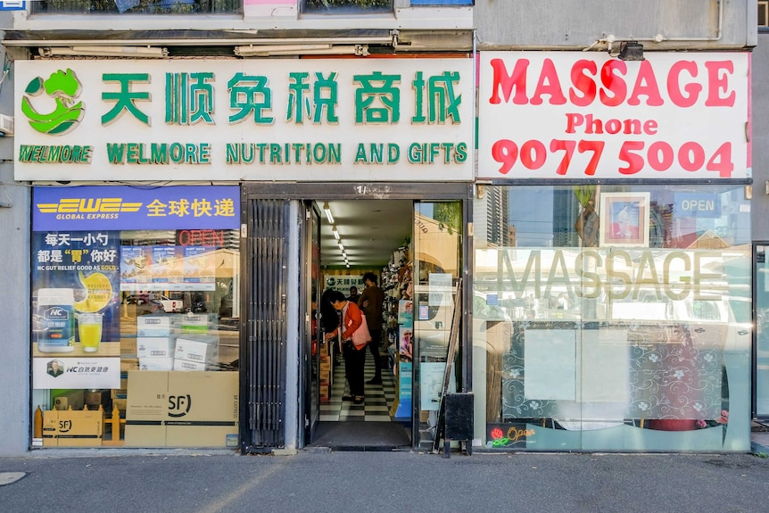 """The shopfront of a daigou specialty shop with a sign saying """"Welmore nutrition and gifts""""."""