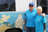Mike and Judy Kendrick stand next to their caravan that is painted with a seascape