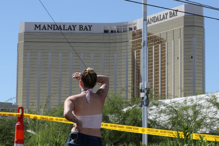 A lady looks past police tape up at the Mandalay Bay hotel with broken windows.
