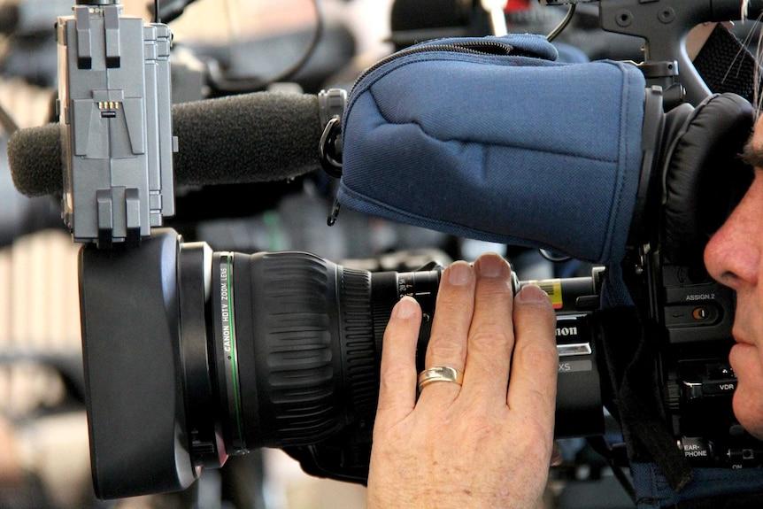 A TV camera operator adjusts the focus at a news job.