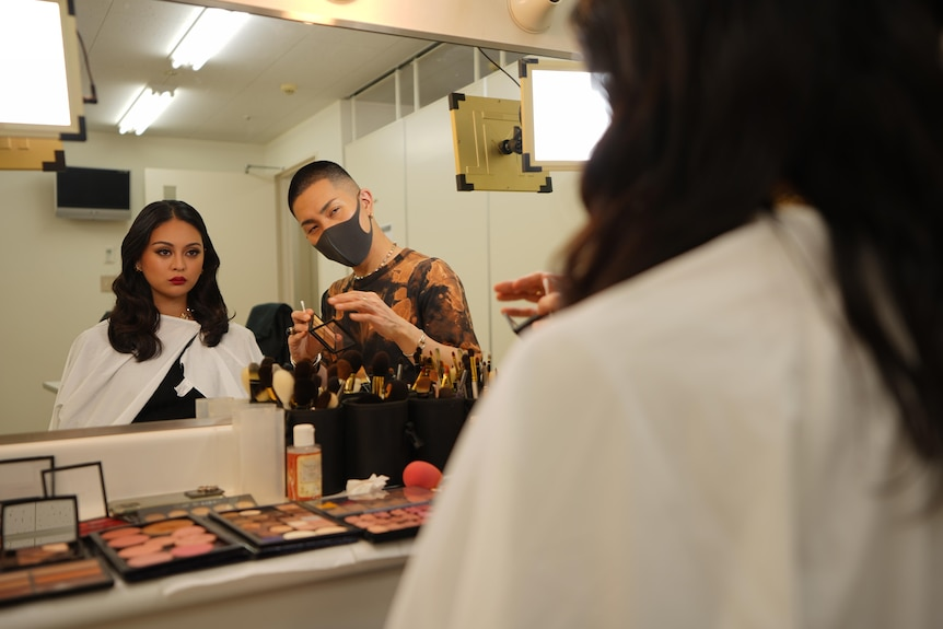 A man in a face mask holding a makeup brush looks in the mirror at a young woman sitting in a chair