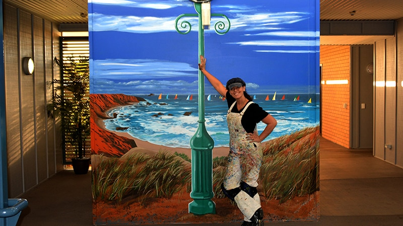 Sharron Tancred leans against a mural of a ocean scene that features a lamp post.