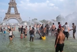 Hundreds of people play in the waters of a fountain in front of the Eiffel Tower.