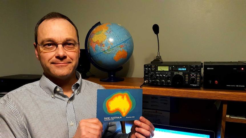 Kevin De Reus sits in his office with his shortwave radio