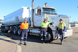 A white haulage truck with three men standing in front of it