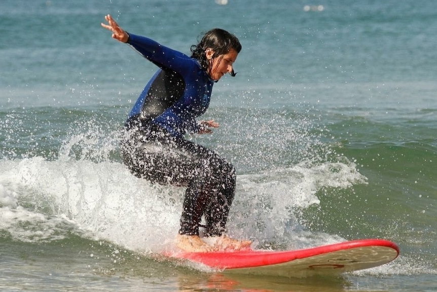 Jess Bart surfing in the waves to depict taking an adult gap year.