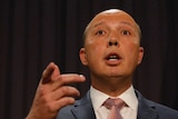 The photo is taken from beneath Mr Dutton, who is standing at the lectern and pointing with his right hand. There are two flags.