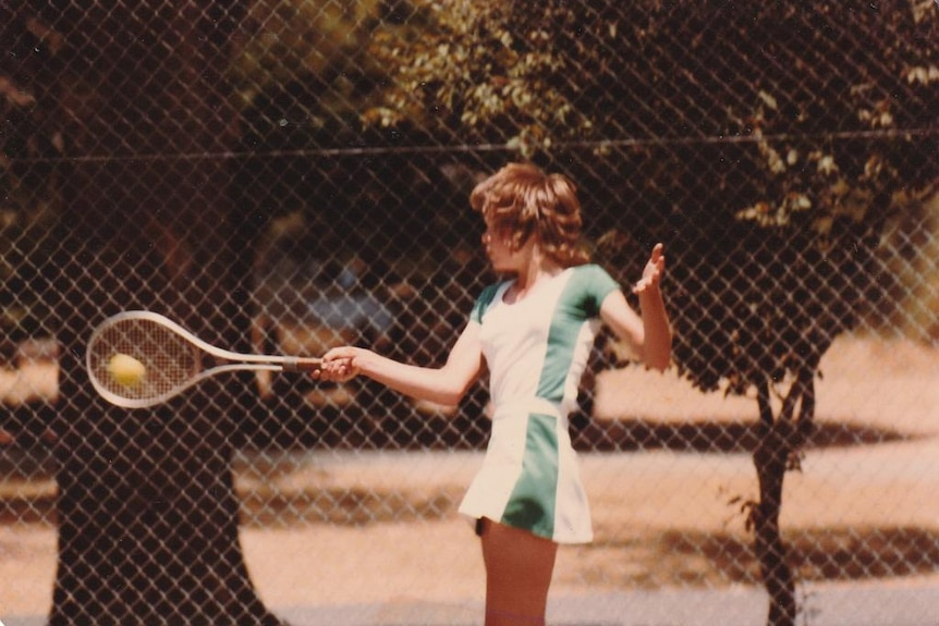 A photograph scan of a girl about age 10 playing tennis wearing a green skirt