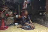 Chan Nareth sits on the floor of her house.